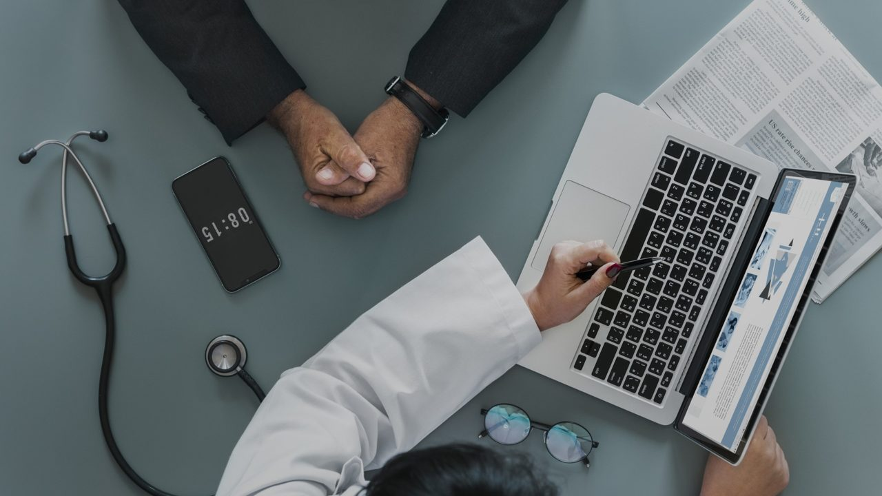 Physician reviewing medical billing and coding with patient